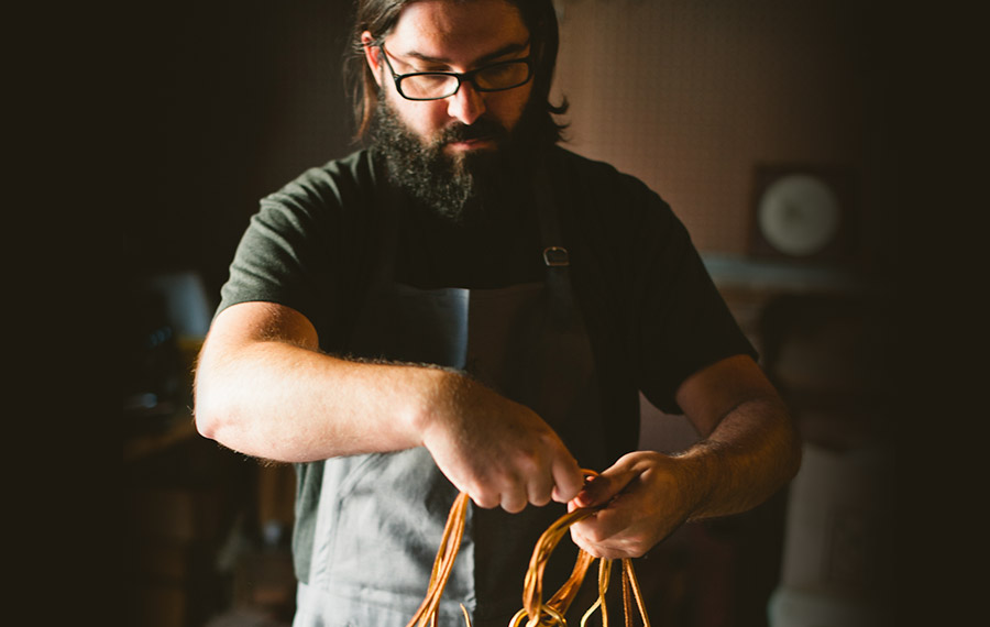 Photo of a bearded man working with leather