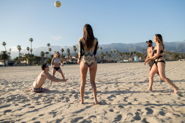Photo of several people playing volleyball on the beach